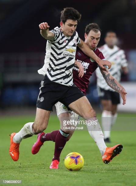 Harry Maguire of Manchester United is challenged by Ashley Barnes of Burnley during the Premier League match between Burnley and Manchester United at...