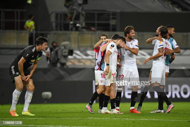Harry Maguire of Manchester United looks dejected following his sides defeat as Munir El Haddadi and Franco Vazquez of Sevilla FC celebrate following...