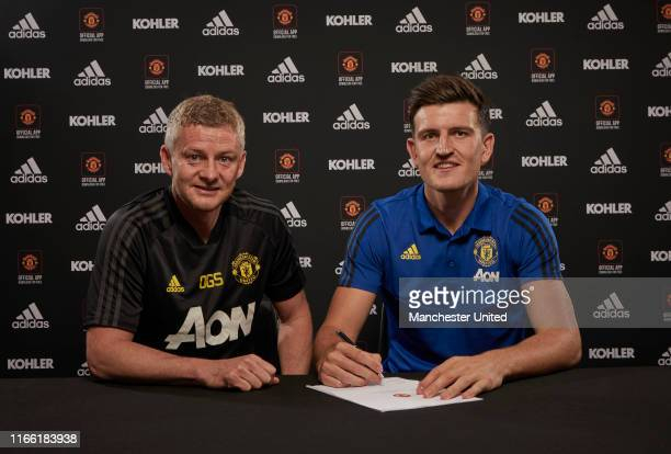 Harry Maguire of Manchester United poses with Manager Ole Gunnar Solskjaer after signing for the club at Aon Training Complex on August 04, 2019 in...