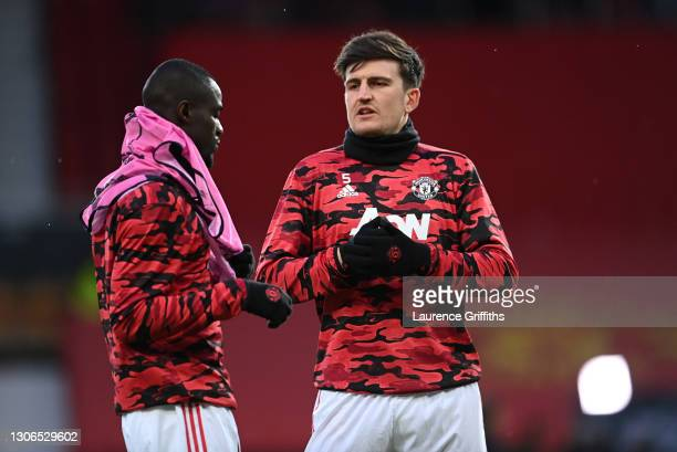 Harry Maguire of Manchester United talks to teammate Eric Bailly as they warm up prior to the UEFA Europa League Round of 16 First Leg match between...