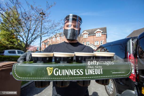 Harry McKeaveney from The Hatfield House bar wearing PPE of a face mask and gloves poses for a photograph as he delivers pints of Guinness poured...