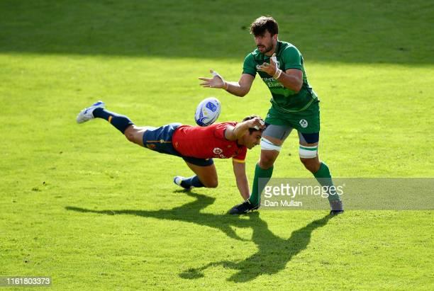 Harry McNulty of Ireland offloads under pressure from Francisco de Paula Hernandez Jiminez of Spain during the Group B match between Ireland and...