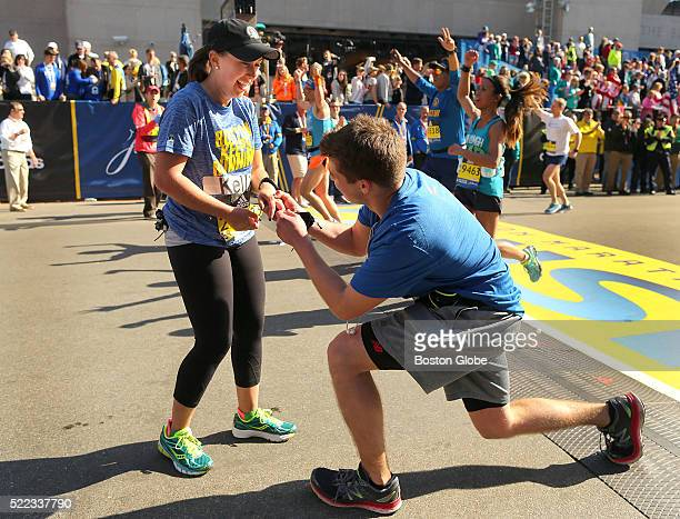 Harry Moulton kneels and puts a ring on the finger of Kellie Marshall who he proposed to after they crossed the finish line of the 120th Boston...