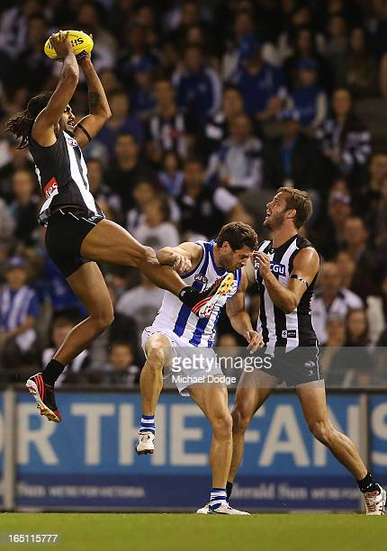 Harry O'Brien of the Magpies takes a high mark over Sam Gibson of the Kangaroos during the round one AFL match between the North Melbourne Kangaroos...