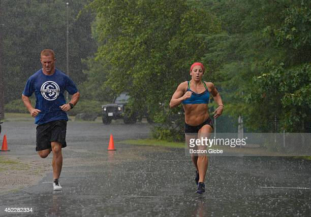Harry Palley and Rachel Martinez both instructors at CrossFit New England of Natick Mass train under the rain Martinez is getting ready to travel to...