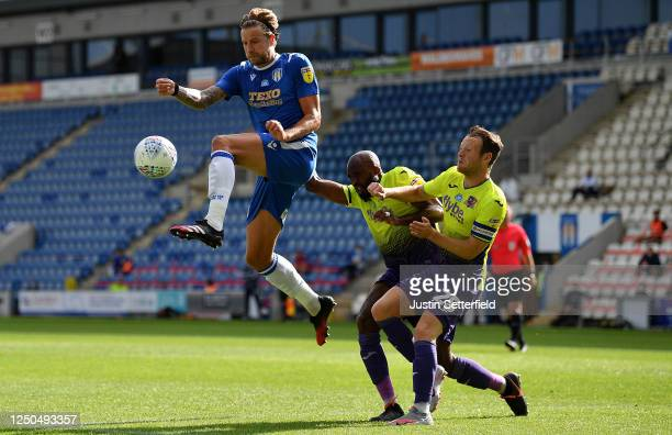 Harry Pell of Colchester United battles for possession with Nigel Atangana and Jake Taylor of Exeter City during the Sky Bet League Two Play Off...
