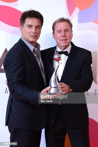 Harry Redknapp and John Barrowman pose with The Bruce Forsyth Entertainment Award for I'm A Celebrity… Get Me Out Of Here in the winners room during...