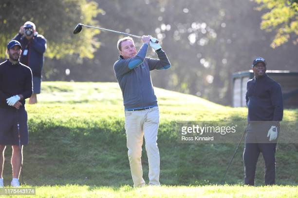 Harry Redknapp tees off as Jamie Redknapp and Ian Wright look on during the ProAm tournament prior to the start of the BMW PGA Championship at...
