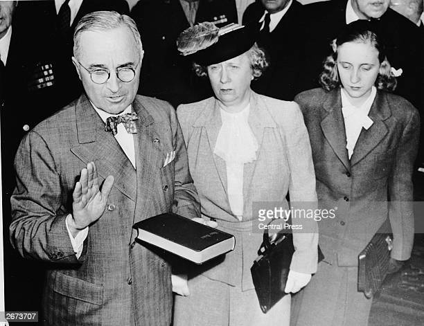 Harry S Truman takes the oath at the start of his term of office as the 33rd president of the United States Standing beside him are his wife Bess and...