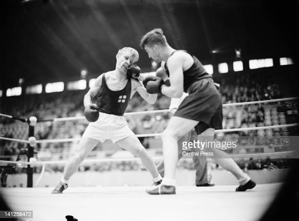Harry Siljander of Finland in the ring with George Hunter of South Africa during match 3 of the quarterfinals of the men's lightheavyweight boxing at...