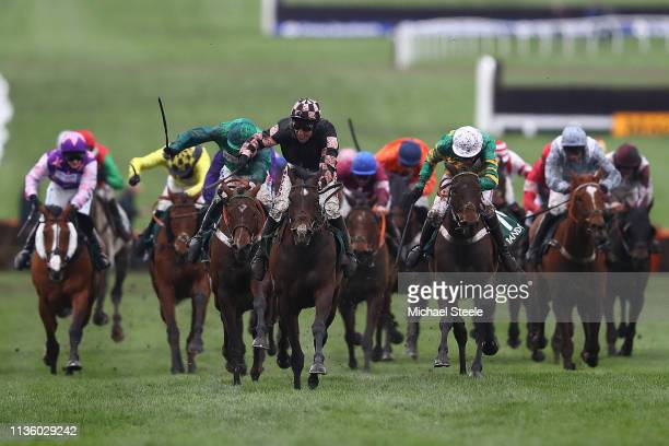 Harry Skelton celebrates winning the The Randox Health County Handicap Hurdle Race with horse Ch'tibello ahead of Daryl Jacob and horse We Have A...