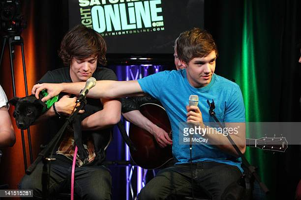 Harry Styles and Liam Payne from the band One Direction perform with a puppy at Radio Station Q102 iHeartRadiod Performance Theater March 17, 2012 in...