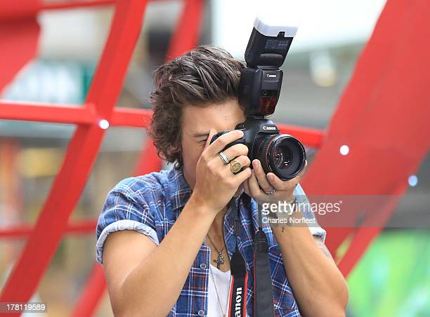Harry Styles of One Direction takes a photo of his adoring fans at NBC's Today at Rockefeller Center on August 23 2013 in New York City