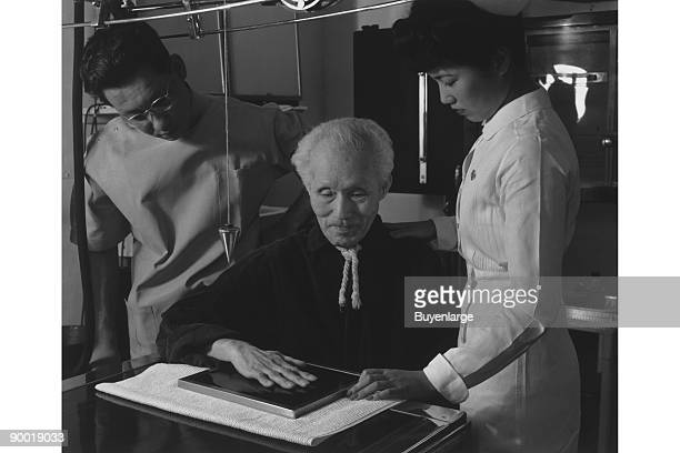 Harry Sumida rests his hand on an xray plate while nurse and technician look on Ansel Easton Adams was an American photographer best known for his...