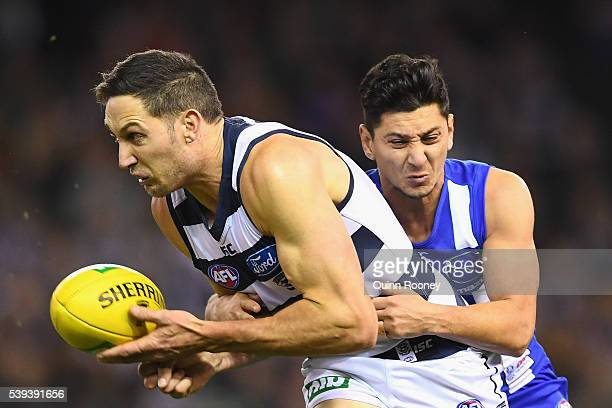 Harry Taylor of the Cats handballs whilst being tackled by Robin Nahas of the Kangaroos during the round 12 AFL match between the Geelong Cats and...