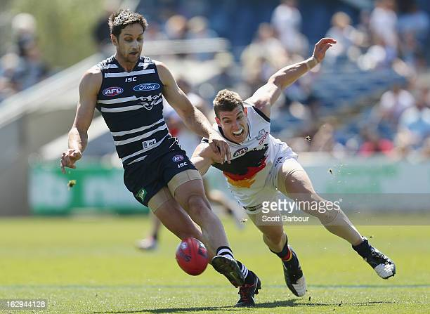Harry Taylor of the Cats kicks the ball as Josh Jenkins of the Crows attempts to tackle during the round two AFL NAB Cup match between the Geelong...