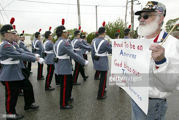Harry Vogelei from Pottstown PA holds up a sign as cadets from Valley Forge Military Academy pass by in a Delaware County parade to honor those who...