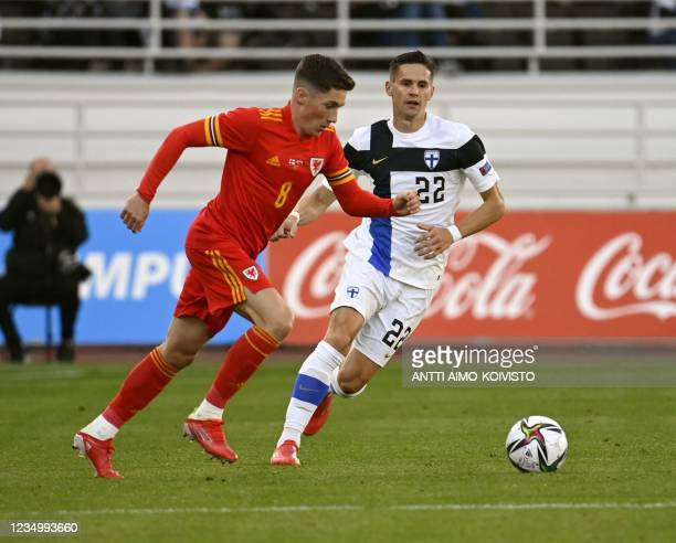 Harry Wilson of Wales and Finland's Jukka Raitala vie for the ball during the international friendly football match Finland vs Wales at the Olympic...