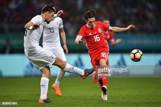 Harry Wilson right of Wales national football team kicks the ball to make a pass against players of Uruguay national football team in their final...