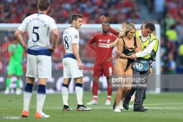 Harry Winks of Spurs looks on as a female streaker is escorted off the pitch by a steward during the UEFA Champions League Final between Tottenham...