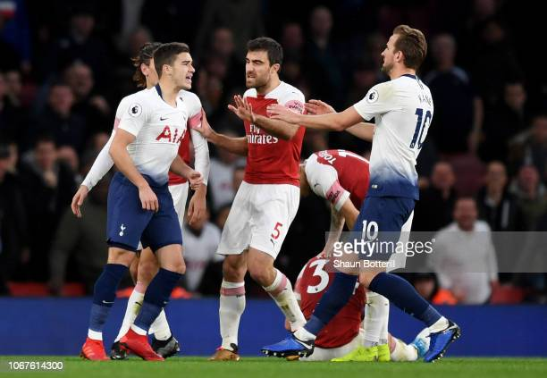 Harry Winks of Tottenham Hotspur and Harry Kane of Tottenham Hotspur clash with Sokratis Papastathopoulos of Arsenal during the Premier League match...