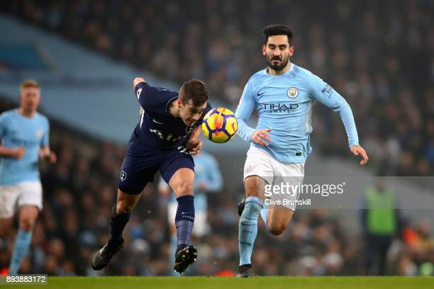 Harry Winks of Tottenham Hotspur heads the ball while under pressure by Ilkay Gundogan of Manchester City during the Premier League match between...