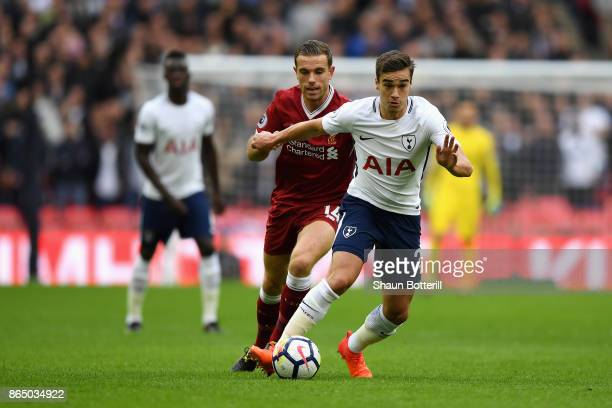Harry Winks of Tottenham Hotspur is put under pressure by Jordan Henderson of Liverpool during the Premier League match between Tottenham Hotspur and...