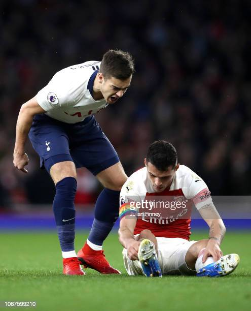 Harry Winks of Tottenham Hotspur reacts to Granit Xhaka of Arsenal during the Premier League match between Arsenal FC and Tottenham Hotspur at...