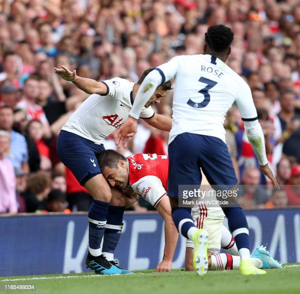 Harry Winks of Tottenham receives the head of Sokratis of Arsenal in an unusual tackle during the Premier League match between Arsenal FC and...