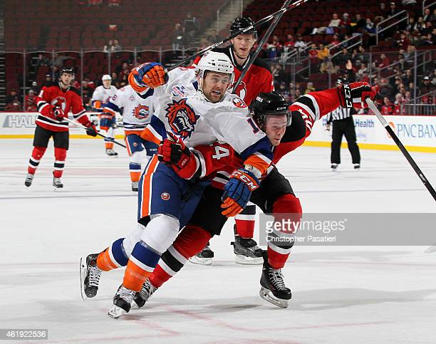 Harry Zolnierczyk of Bridgeport Sound Tigers and Reece Scarlett of Albany Devils skate during the first period of an American Hockey League game at...