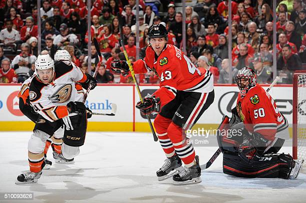 Harry Zolnierczyk of the Anaheim Ducks and Viktor Svedberg of the Chicago Blackhawks watch for the puck in front of goalie Corey Crawford in the...