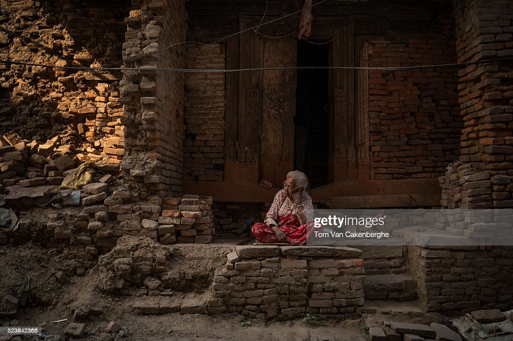 Harsha Maya sits in front of her severely damaged home in the center of Bhaktapur on April 24, 2016 in Kathmandu, Nepal. She doesn't know her age but neighbors say she is very old old. Harsha Maya says she is not afraid of earthquakes as she survived the previous serious earthquake in 1934, which she remembers and prefers to stay in her home, regardless of the condition. A 7.8-magnitude earthquake struck Nepal close to midday on April 25 lasts year. It was knowned to be Nepal's worse earthquake in history as an estimated 9,000 people died and countless towns and villages across central Nepal were destroyed. Based on reports, the government promised 2,000USD to affected households but has only paid out a fraction of the amount so far and an estimated 660,000 families are still living in sub-standards temporary shelters or unsafe accommodations one year later.