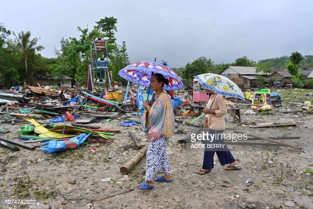Hartati , whose house was destroyed by a tsunami, walks with a relative in the Sumber Jaya village in Sumur, Pandeglang, Banten province on December...