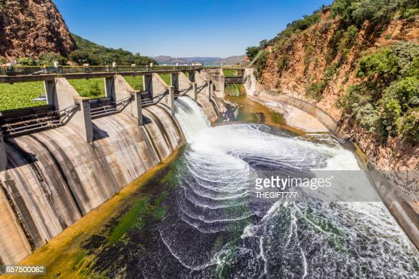 hartebeespoort dam reservoir wall with open sluice gate - reservoir stock pictures, royalty-free photos & images