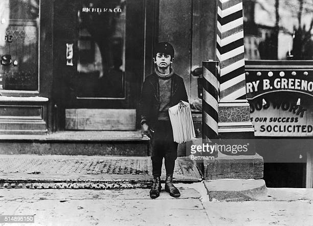 A Hartford newsboy sells papers on a city sidewalk