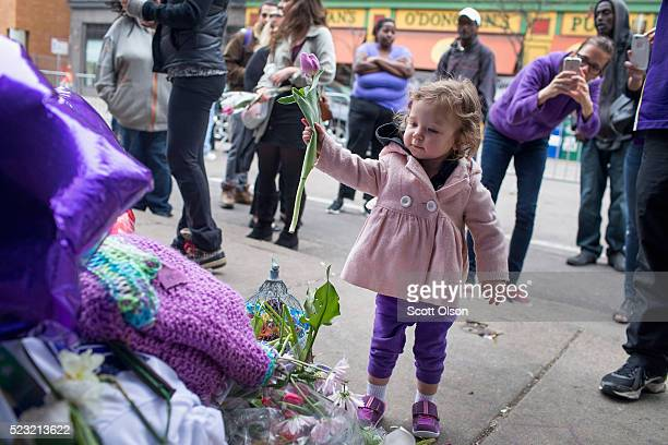 Hartley Hokuf leaves a flower at a memorial to Prince outside the First Avenue nightclub while her mother Melissa takes a picture on April 22 2016 in...