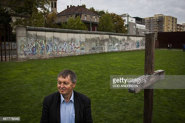 Hartmut Richter poses for pictures along remains of the 'Wall' along Bernauer strasse in Berlin on October 8, 2014. Richter fled the communist German...
