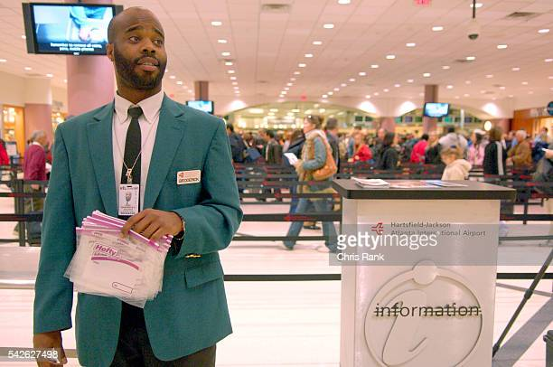 HartsfieldJackson International Airport employee Broderick Peek hands out approved containers to travlers as they prepare to go through security...