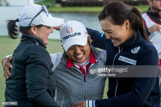 Haru Nomura of Japan is embraced by Caroline Masson of Germany and In Gee Chun of South Korea following her victory at the Volunteers of America...