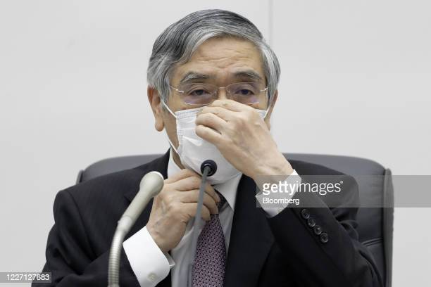 Haruhiko Kuroda, governor of the Bank of Japan , adjusts a protective face mask during a news conference at the central bank's headquarters in Tokyo,...