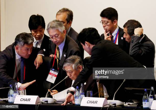 Haruhiko Kuroda, governor of the Bank of Japan , center, reads a document during the Group of 20 finance ministers and central bank governors meeting...