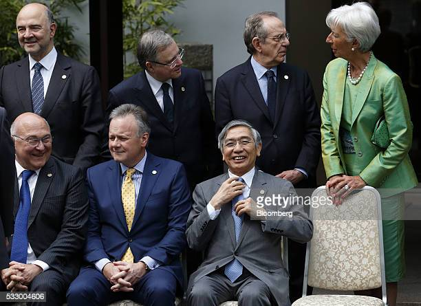 Haruhiko Kuroda governor of the Bank of Japan front row right adjusts his tie during a photo session ahead of the Group of Seven finance ministers...