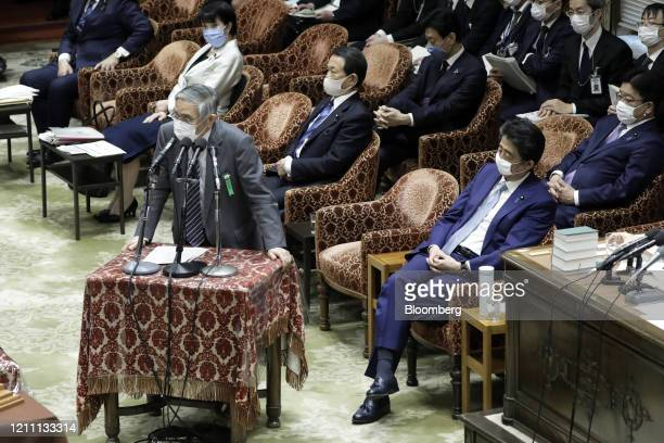 Haruhiko Kuroda, governor of the Bank of Japan , left, wears a protective mask as he speaks while Shinzo Abe, Japan's prime minister, listens during...