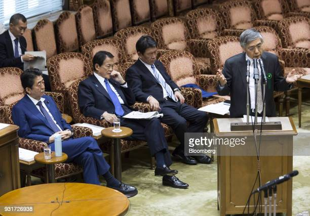 Haruhiko Kuroda governor of the Bank of Japan right speaks as Shinzo Abe Japan's prime minister left Taro Aso Japan's finance minister second left...