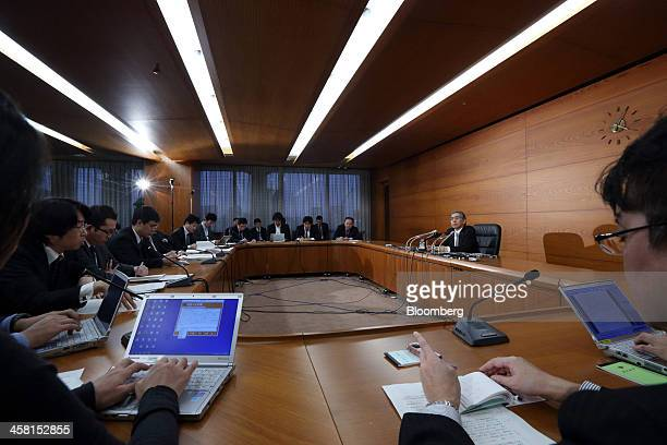 Haruhiko Kuroda governor of the Bank of Japan right speaks during a news conference at the central bank's headquarters in Tokyo Japan on Friday Dec...