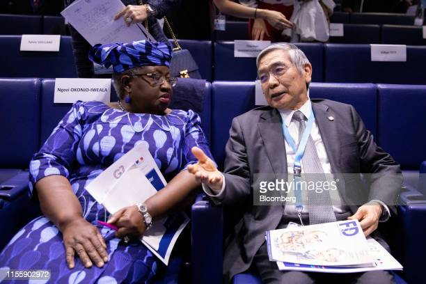 Haruhiko Kuroda governor of the Bank of Japan right speaks with Ngozi OkonjoIweala former finance minister of Nigeria during the 75th anniversary of...