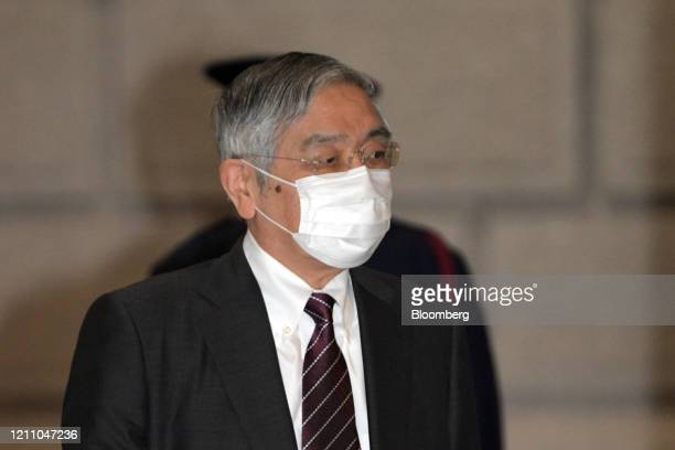 Haruhiko Kuroda governor of the Bank of Japan wearing a protective mask arrives at the central bank's headquarters in Tokyo Japan on Monday April 27...