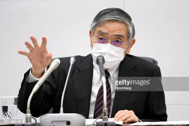 Haruhiko Kuroda, governor of the Bank of Japan , wearing a protective mask gestures as he speaks during the central bank's headquarters in Tokyo,...