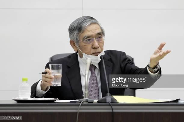 Haruhiko Kuroda, governor of the Bank of Japan , wearing a protective face mask, takes a question during a news conference at the central bank's...