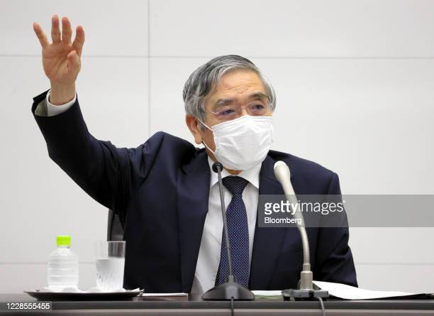 Haruhiko Kuroda, governor of the Bank of Japan , wearing a protective face mask, gestures as he speaks during a news conference at the central bank's...